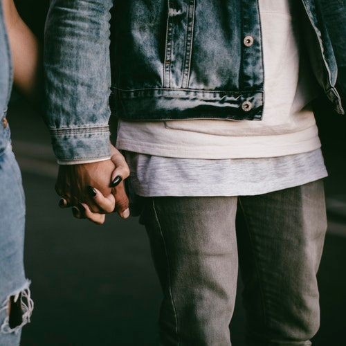 couple wearing denims holding hands
